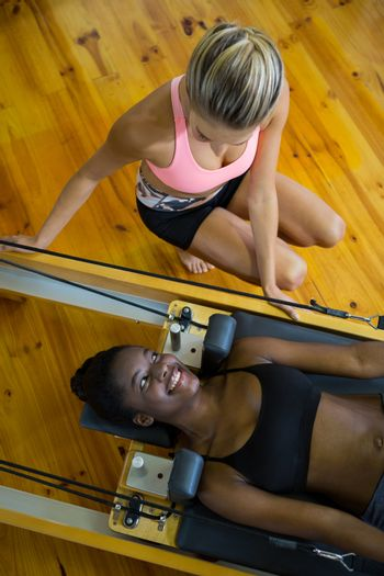 Trainer assisting woman with pilates on reformer