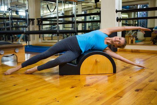 Fit woman doing pilates on arc barrel