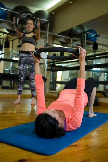 Determined women exercising with pilates ring