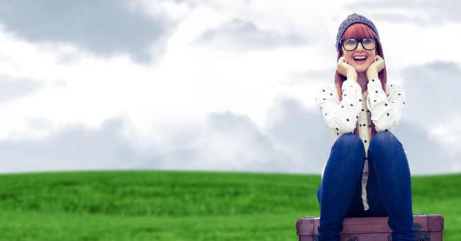 Woman seating on a Luggage against a field background
