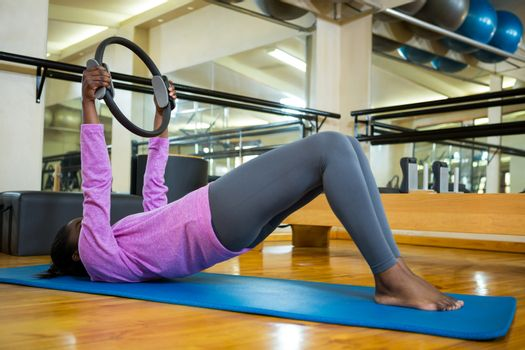 Fit woman exercising with pilates ring on mat