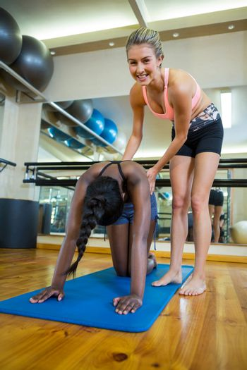 Smiling trainer assisting a woman while practicing pilates