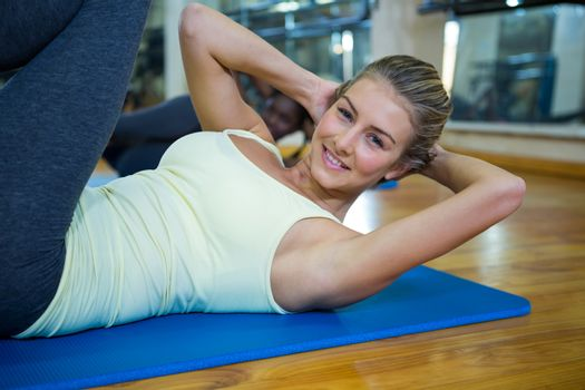 Portrait of smiling fit woman doing stretching exercise on mat in fitness studio