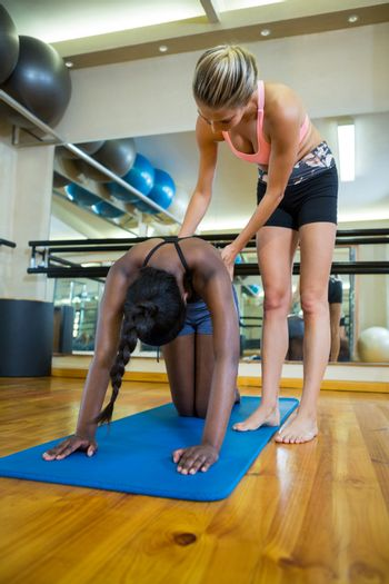Trainer assisting a woman while practicing pilates