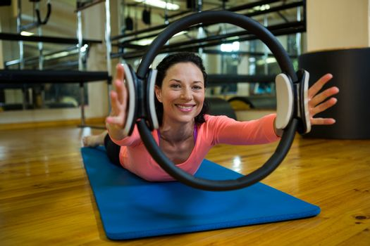 Portrait of happy woman exercising with pilates ring