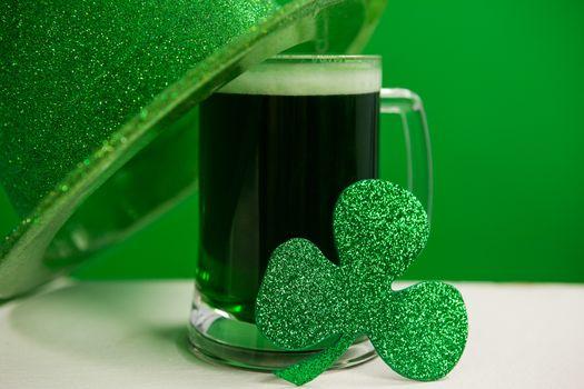 St Patricks Day leprechaun hat with mug of green beer and shamrock