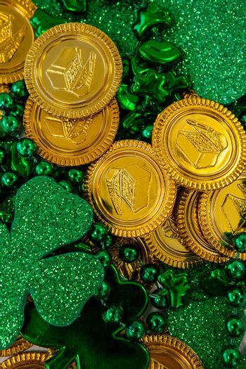 St. Patricks Day close-up of chocolate gold coins, beads and shamrocks