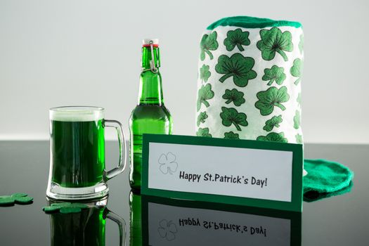 Green beer with shamrock, leprechaun hat and placard of St Patricks Day