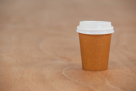 Disposable coffee cup on wooden background
