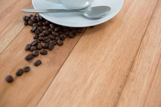 Roasted coffee beans with saucer and spoon
