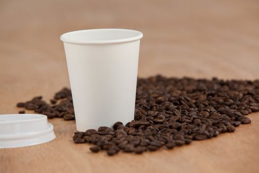 Coffee beans and black coffee in disposable cup