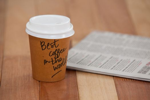 Close-up of disposable coffee cup and newspaper