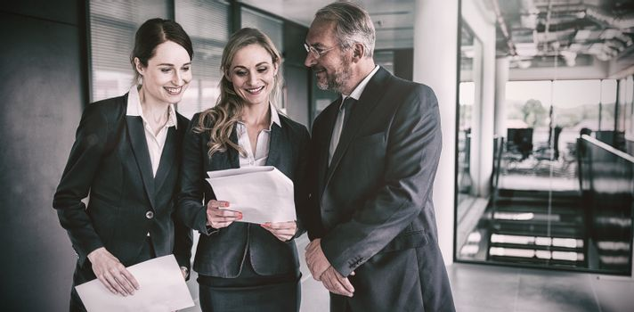 Happy businesspeople discussing over report