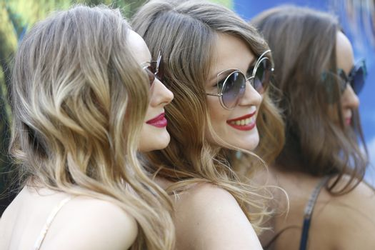 The faces of three models.Women in sunglasses
