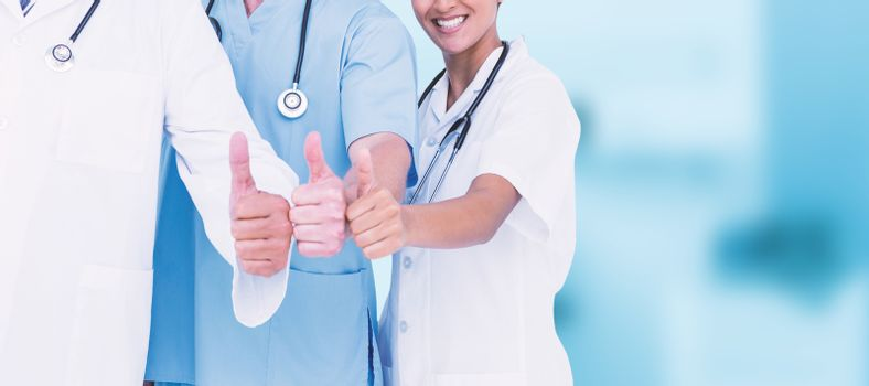 Portrait of smiling doctors with thumbs up against dental equipment
