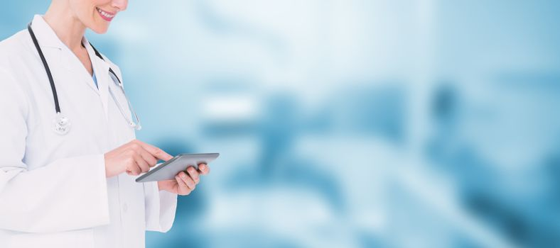 Blonde doctor using tablet pc against dental equipment