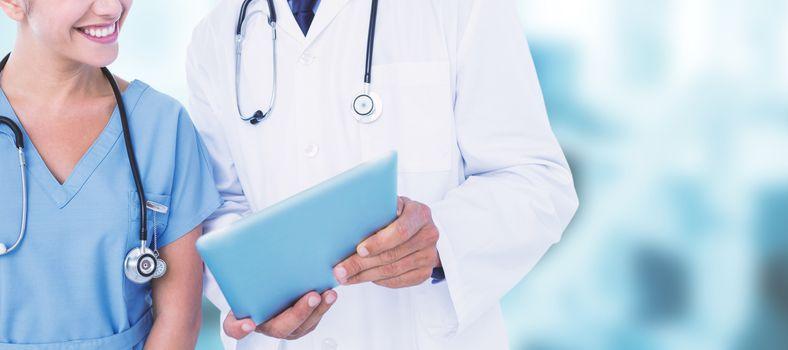 Smiling male doctor with nurse using digital tablet against dental equipment