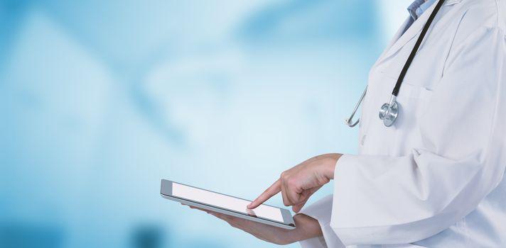 Midsection of female doctor using digital tablet against dental equipment