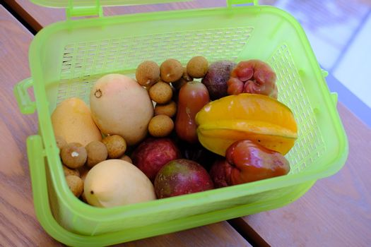 Green Plastic container box full with fresh ripe tropical fruits for transportarion. Tourism concept. Top view.