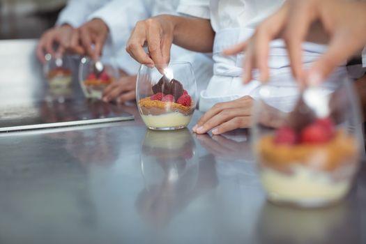 Chefs finishing dessert in glass at restaurant