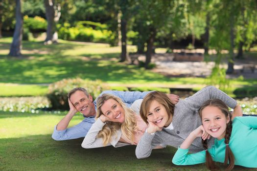 family laying on the grass