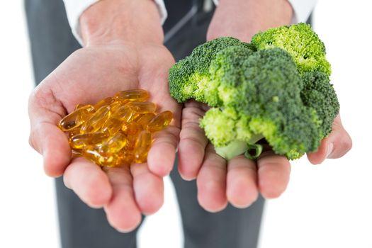 Businessman holding broccoli and vitamin pills