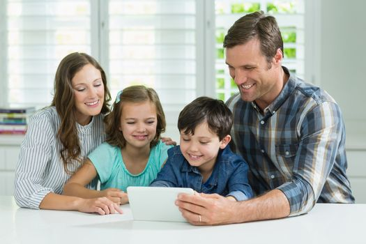 Smiling family using digital tablet in living room at home