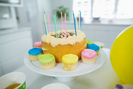 Close up of birthday cake on stand with cup cake and candles