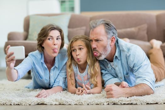 Family taking selfie from mobile phone while lying together on carpet in living room at home