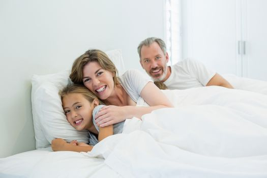 Portrait of happy family lying together on bed in bedroom at home