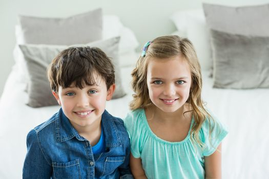 Portrait of smiling siblings sitting on sofa in living room at home