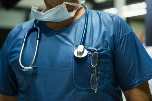 Mid section of male surgeon in scrubs