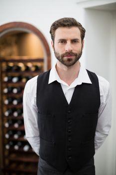 Portrait of male waiter standing in the restaurant