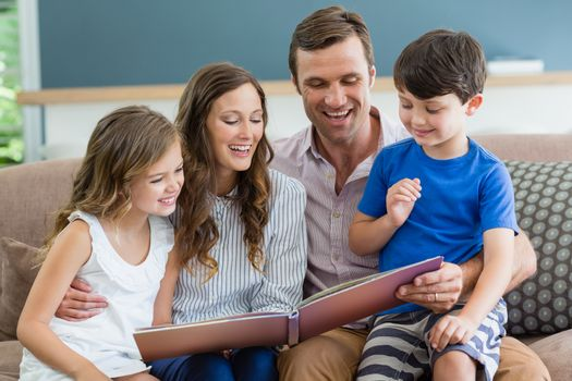 Smiling family sitting on couch looking at photo album in living room at home