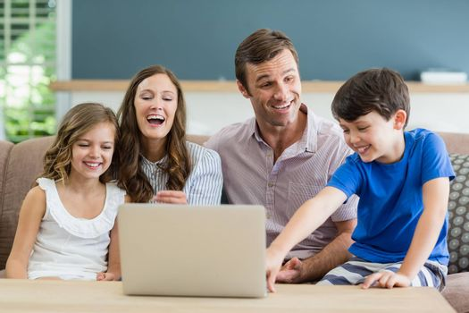 Smiling family sitting on sofa using laptop in living room at home