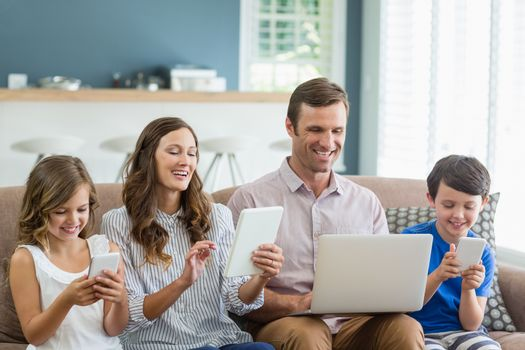 Smiling family using digital tablet, phone and laptop in living room at home