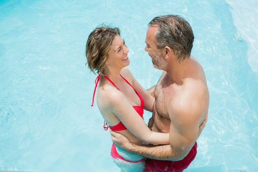 Happy couple romancing in swimming pool on a sunny day