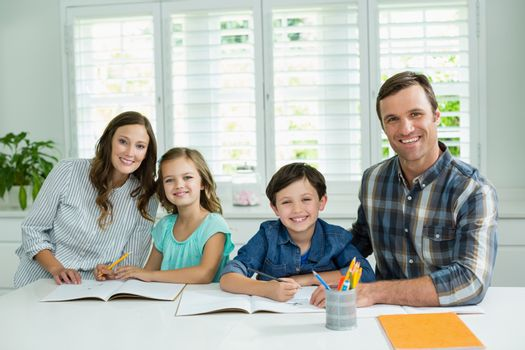 Portrait of smiling family studying together in living room at home