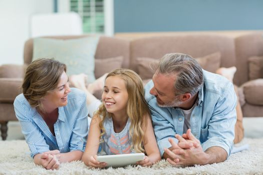 Happy family using digital tablet while lying on floor in living room at home