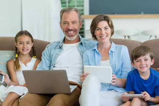 Happy family using mobile phone, digital tablet and laptop in living room at home