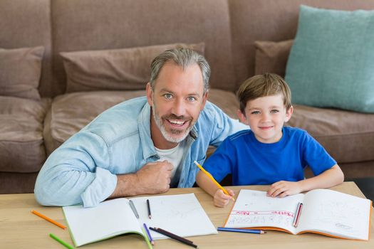 Father helping his son with homework in living room at home