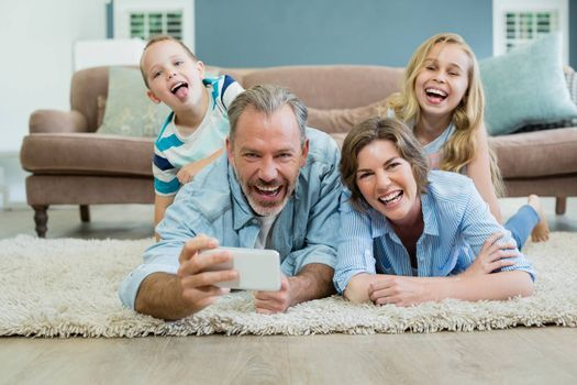Family taking selfie while lying together on the carpet in living room at home