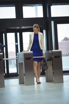 Businesswoman passing through turnstile gate