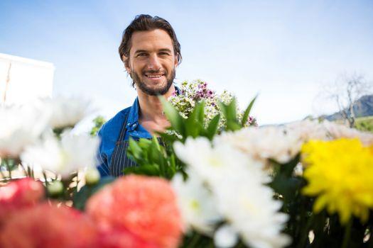 Smiling florist holding bunch of flower in florist shop