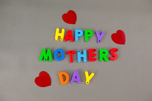 Alphabets displaying happy mothers day on grey background