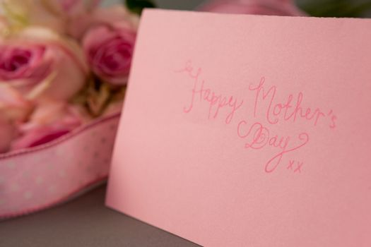 Close-up of happy mothers day card on grey background