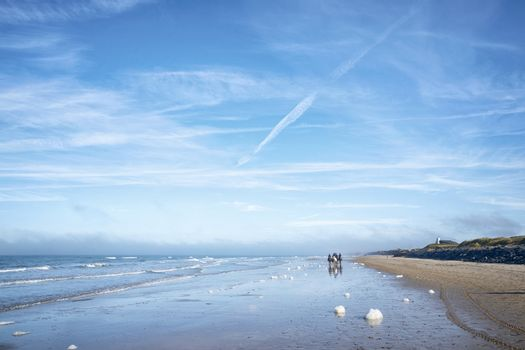 Horseback riders on a beach in the summer under a blue sky with white clouds