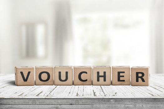 Voucher sign in a bright room on a white painted table made of wood