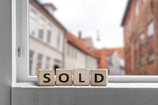 Sold word made with cubes in a window in a city with a view to buildings