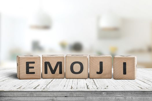 The word emoji on a wooden sign in a bright room on a white desk